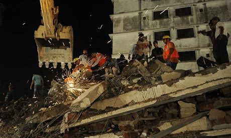 Rescuers work in the ruins of a building that collapsed in Mumbai, killing dozens